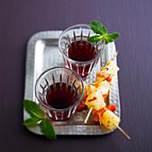 Apfelwein-Brombeer-Cocktail dazu Ananas-Garnelen-Spießchen