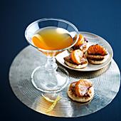 Sunset-Cocktail dazu Mini-\nBlinis mit Foie Gras und Mandarine