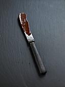 Messer mit Resten von geschmolzener Schokolade auf dunklem Untergrund