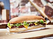 Länglicher Beefburger mit Käse und Sauce Bearnaise
