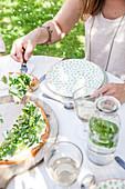 Frischkäsetarte mit grünem Gemüse auf Tisch im Freien