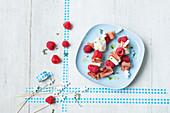 Skewers of mozzarella, raw ham and raspberries