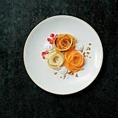 Süße Spaghetti-Nester aus Melone, Apfel und Birne mit  Mandelcreme und Granatapfel