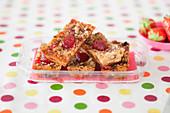 Müsliriegel mit Erdbeeren in Plastikschale auf gepunkteter Tischdecke