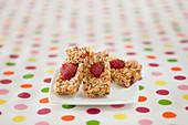 Müsliriegel mit Erdbeeren auf gepunkteter Tischdecke