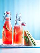 Wassermelonenlimonade in Bügelflaschen daneben ein Sandwich