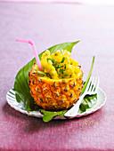 Ananassalat in ausghöhlter Ananas serviert