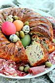Pikanter Osterkranz mit Speck dekoriert mit Eiern und Oliven