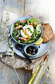 Bowl mit grünem Gemüse, Garnelen und wachsweichem Ei