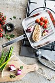Gegrilltes Hähnchenfilet mit Kirschtomaten und roten Zwiebeln in Grillpfanne