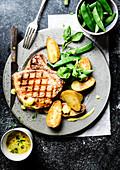 Gegrilltes Schweinekotelett, mit Kartoffeln, Zuckerschoten und Gurkensauce