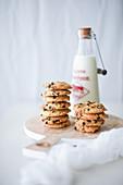 Chocolate Chips Cookies auf Holzbrett dahinter eine Milchflasche