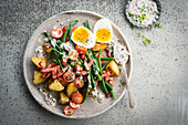 Salad with potatoes, bacon, green beans and boiled eggs