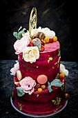 Zweistöckige rote Geburtstagstorte dekoriert mit Büten und Macaron