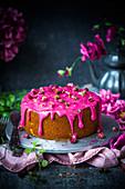 Kokoskuchen verziert mit pinkfarbener Rosenwasserglasur und Rosenblüten