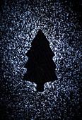 Abdruck eines Tannenbaums auf schwarzem Untergrund