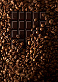 Composition of coffee beans with a dark chocolate bar