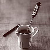Küchenthermometer in einer Tasse mit geschmolzener Schokolade