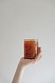 Hand hält ein Glas Orangenmarmelade