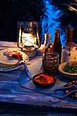 Fajitas mit Zutaten auf Tisch im Freien bei Abendstimmung
