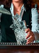 Barkeeper gibt Eiswürfel in ein Cocktailglas