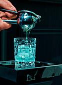 Barkeeper presst Saft mit Presse in Cocktailglas