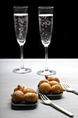 Kabeljaukrapfen dahinter zwei Champagnergläser