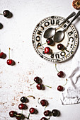 Frische Kirschen und ein Teller mit der Aufschrift 'Bon Jour'