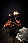 Ein Stapel Schokoladenpfannkuchen mit Wunderkerzen