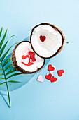 Halbierte Kokosnuss gefüllt mit Papierherzchen