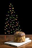 Italienischer Panettone im Hintergrund leuchtender Weihnachtsbaum