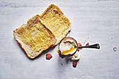 Zwei Scheiben Toastbrot und ein weichgekochtes Ei im Eierbecher