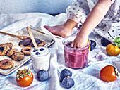 Kleines Kind hält Hand in Fruchtsmoothie