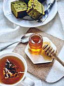 Tea Time mit Tasse Tee, Honig und Kuchen