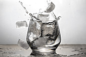Ice cubes falling into a glass of water.