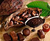 Stillleben mt Kakaoschote, Kakaobohnen, flüssiger Schokolade und Schokoladenkonfekt