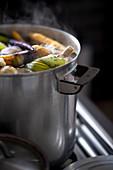 Dampfender Gemüseeintopf mit Fleisch im Kochtopf