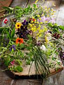 Frische Kräuter und Blüten auf Holzbrett