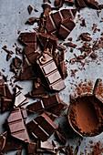 Gehackte Schokoladenstücke und Vintage-Sieb mit Kakaopulver