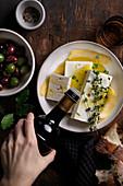 Feta in Olivenöl, Thymian, Lorbeer und Zitronenschale marinieren