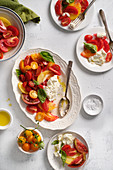 A salad of yellow, orange and red tomatoes with fresh basil and burrata cheese, seasoned with salt, black pepper and olive oil
