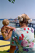 Older women sitting at lake, Starnberger See, Bavaria, Germany