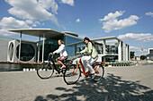 Two young women cycling cross-town, Berlin, Germany