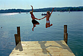 Young couple jumping from a jetty, Starnberger See, Bavaria, Germany