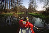 Young woman kayaking on Zschummi Kanal, Spreewald, Brandenburg, Germany