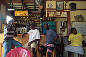 Three native men sitting at a bar, St. Lucia, Caribbean