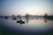 Fisherman in fishing boat at dawn, Weitmannsee Lake, Bavaria, Germany