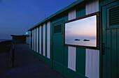 Mirror at bathhouse wall reflecting the sunset, Capri, Italy