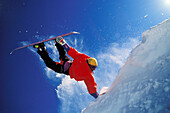 Acrobatic jump of snowboarder