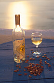Bottle and glass of wine in the evening light, Santorin, Greece, Europe